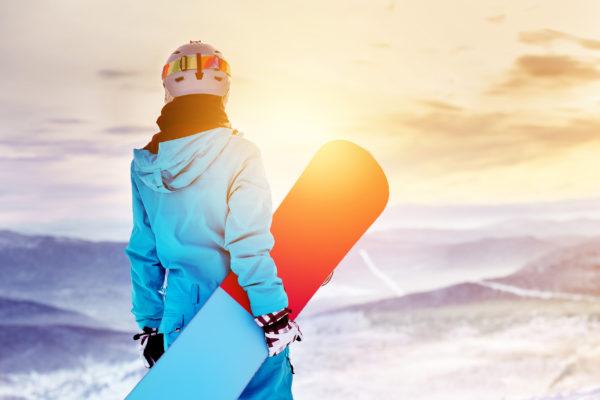Snowboarderin Sonnenuntergang Schnee
